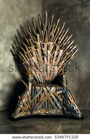 Vertical closeup vintage image of a swords throne at textured studio wall background. #1048791320