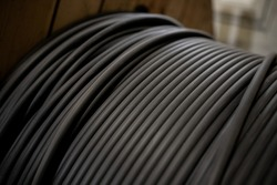 Vertical coils ndustrial wires. Many turns of main electrical cable is closeup. Roll of outdoor fiber optic signal shielded cables. Wooden Coils of powerful black telecommunications wire