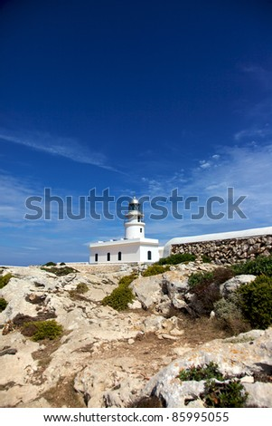 Vertical color image of a white lighthouse in the distance. Rocks and plants in the bottom part of the image and a beautiful blue sky on top.