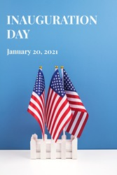 Vertical composition with USA flags on white table against blue wall background, copyspace for your text. Inauguration Day 2021 concept