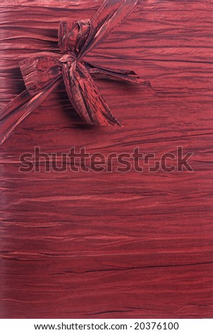 Vertical crimson red fabric textured gift background with a ribbon and box in the upper left corner running diagonally.