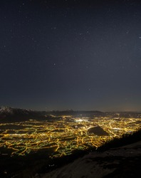 vertical crop panorama of salzburg at night, seen from mt. gaisberg