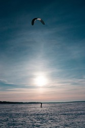 Vertical dreamy photo with an alone ski kiter riding on a frozen snowy lake at winter cold sunset against sun, shining over horizon in the blue sky
