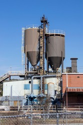Vertical exterior of a brick and metal industrial building with storage silos, a dust collection system, and a conveyor, behind a barbed-wire fence.