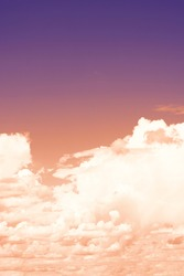 Vertical format of toned background in vintage style. Purple colored natural background with gradient sky and lots of fluffy cumulus clouds on it.