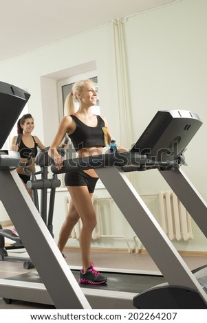 Vertical format Portrait of Two young adult cut sporty women run on machine in the gym centre Beautiful girls with white headphone inside on on wall and window background Copy space for inscription