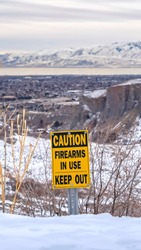 Vertical frame Caution Firearms In Use Keep Out sign on a mountain covered with snow in winter