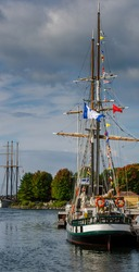Vertical frame of two tall ships moored at port on the St. Lawrence River under a cloudy sky