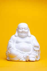 Vertical frame of white smiling porcelain buddha statue sitting in a meditation position. Studio religious figure still life against a seamless yellow background.