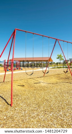 Vertical frame Swings on a park with playground pavilion lake and mountain in the background. Lush trees and opulent homes can also be seen around the recreational area. #1481204729