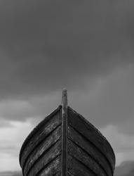 Vertical front view of an old fishing wood boat with rusted nails with dramatic grey storm clouds in the background