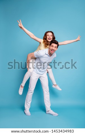 Vertical full length body size view of his he her she nice-looking attractive cheerful cheery playful people wearing casual showing v-sign isolated over bright vivid shine blue green background #1453434983