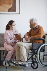 Vertical full length portrait of young female nurse assisting senior man in wheelchair using digital tablet at retirement home, both wearing masks
