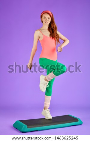 vertical full length view of young pretty fit woman makes intense steps at fitness platform, prefers home workouts, wants to lose some weight, wears 80s retro style colorful aerobics outfit
