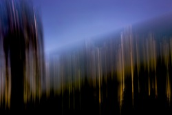 Vertical golden light-streaks with purple sky above and blacked-out shadow area below - abstract motion-blurred background / texture