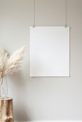 Vertical hanging poster mockup on a neutral coloured wall. Hanging by clips and string. Pampas grass in a large glass vase sitting on a small tree stump prop.