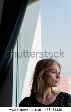 vertical head shot of blond woman looking out of window with sad and melancholic expression below curtain with natural light with clear sky and delicate colors and soft light