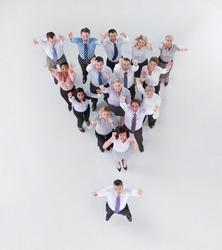 Vertical high angle shot of a group of businesspeople cheering standing in an inverted pyramid formation behind their boss smiling at the camera.