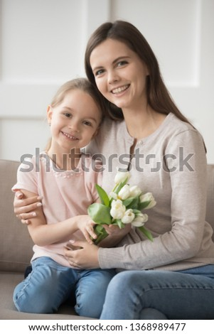 Vertical image family portrait mum hugs small daughter holds white tulips flowers sitting on sofa at home, kid make present for loving mom. Mother day birthday life events holidays celebration concept