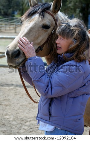 Vertical image of a Baby Boomer era woman showing affection to her horse.