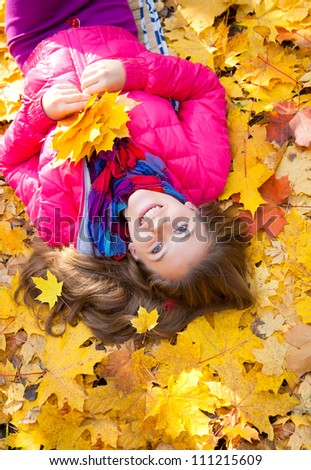 vertical  image of a cheerful girl lying in autumn leaves