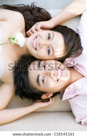 Vertical image of a couple lying head to head, girl holding a white rose