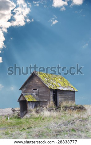 Vertical image of a derelict Eastern Oregon Homestead with sun rays shining through the clouds.