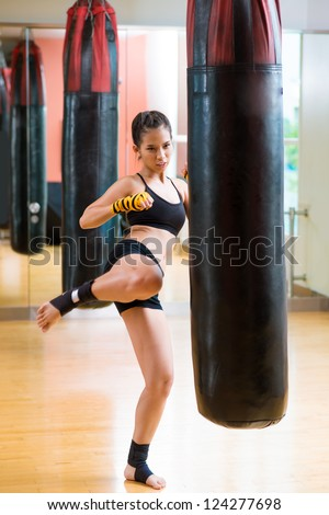 Vertical image of a fit girl practicing her kick