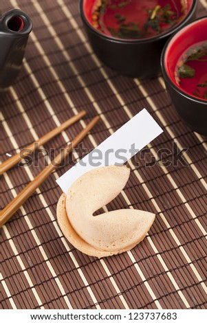 Vertical image of a fortune cookie beside a pair of chopsticks, bowls