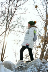 Vertical image of a girl walking in winter forest. People, teens, nature, travel concept.