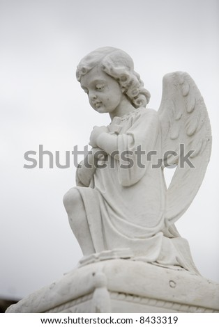 Vertical image of a sculpture of an angel atop a tomb.