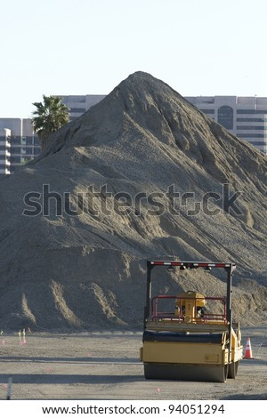 Vertical image of a steam roller dwarfed by a giant mount of asphalt at a construction site.