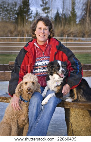 Vertical image of a woman sitting outdoors with her Standard Poodle and Miniature Australian Shepherd. Focus on woman's face.