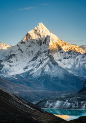 Vertical image of Amadablam mountain peak during sunset and a view of Cholatse glacial lake on the foothills of mountains in Everest region of Nepal.
