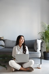 Vertical image of ambitious freelance girl sitting at home with laptop and looking outside window, smiling. Woman working on computer in living room.