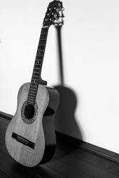 Vertical image of an used, old, cracked classic guitar with dark shadow on the white wall, monochrome image.