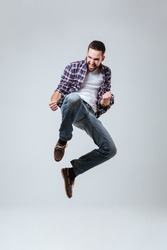 Vertical image of Bearded man in shirt which jumping in studio. Isolated gray background
