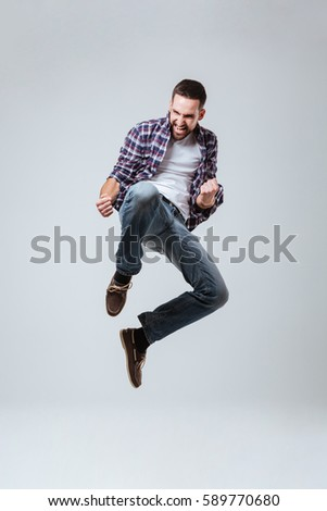 Vertical image of Bearded man in shirt which jumping in studio. Isolated gray background #589770680