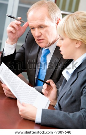 Vertical image of business colleagues sitting at the table and looking pensively at business documents in the office