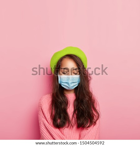 Vertical image of calm ill woman covers nose and mouth with medical mask, has infectious disease, wears protective mask in public place, dressed in fashionbale headgear and pink knitted sweater