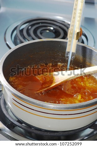 Vertical image of Candy thermometer in saucepan of bubbling apricot juice measures temperature as it reaches boiling point.