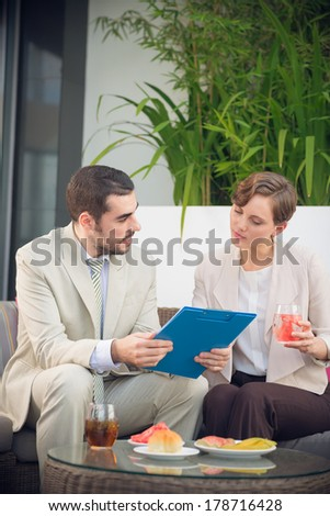 Vertical image of colleagues at a business lunch, the woman listening to the man with attention