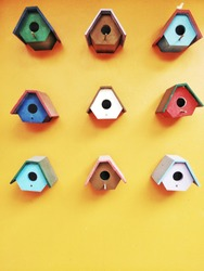 Vertical image of colorful pastel little bird houses on the yellow wall with space for add text at down side of frame
