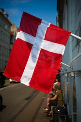 Vertical image of Danish red and white flag  waving in the wind with people sitting on a bench blurred in the background. A small Danish flag waving outside from the right to the left on a sunny day.