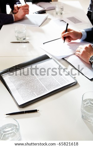Vertical image of document at workplace with human hands during business discussion on background