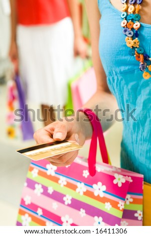 Vertical image of female hand with plastic card giving it to shop assistant