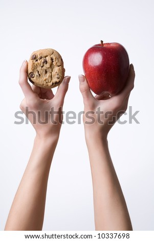 Vertical image of hands holding up a cookie and apple before a white background