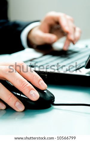 Vertical image of hands pushing keys of a computer mouse and keyboard