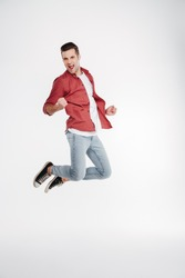 Vertical image of happy man in shirt and jeans which jumping in studio. Full length portrait over white background