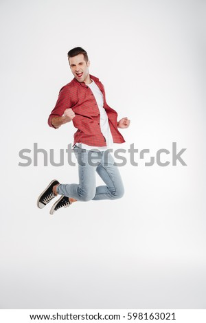Vertical image of happy man in shirt and jeans which jumping in studio. Full length portrait over white background #598163021